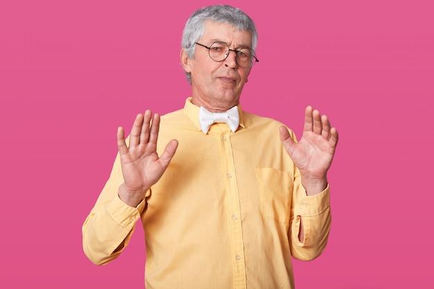 Красивый старший мужчина позирует изолированные на розовый