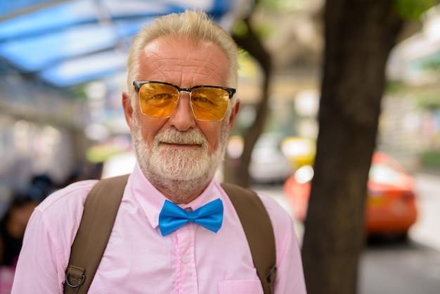 タイ、バンコクの街を探索するハンサムなシニア観光男