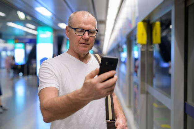 Handsome senior tourist man using phone for directions at the train station