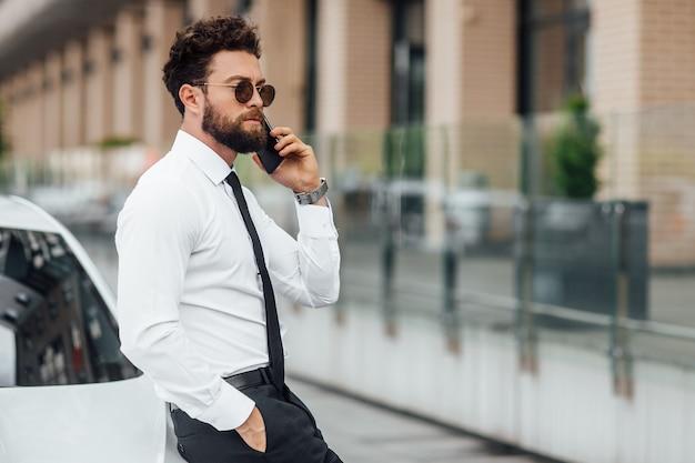 Красивый, серьезный, бородатый бизнесмен в белой рубашке, разговаривает по телефону и стоит возле своей машины на улице на улице города возле современного офисного центра