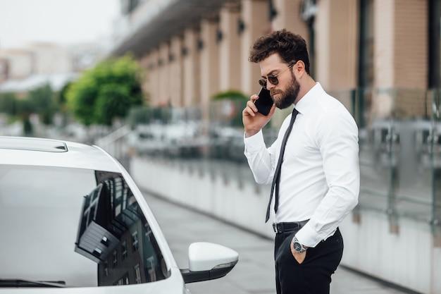 선글라스를 끼고 수염을 기른 잘 생기고 진지한 매니저는 전화로 말하고 현대적인 사무실 센터 근처 도시 거리에 있는 야외에서 차 근처에 서 있습니다.