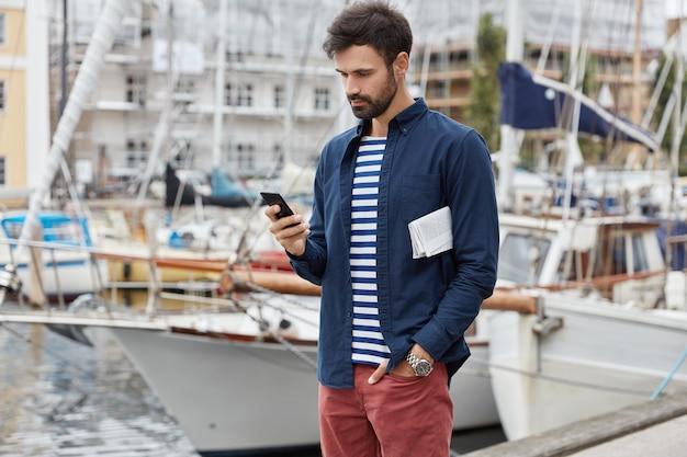 Красивый серьезный бородатый молодой парень идет по гавани