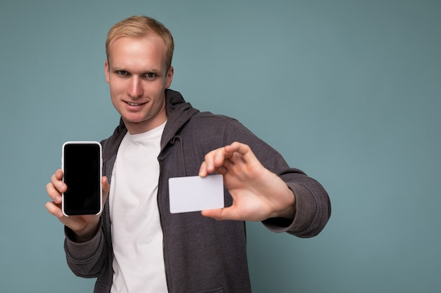 Handsome serious blonde man wearing grey sweater and white t-shirt isolated over blue background wall holding credit card and mobile phone with empty screen for cutout looking at camera.