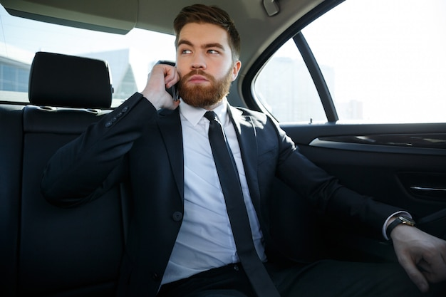 Handsome serious business man talking on mobile phone