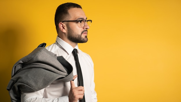 Handsome serious business man with trendy beard dressed in greyish suite posing holding his jacket on his shoulder hanging it behind looking isolated on yellow wall