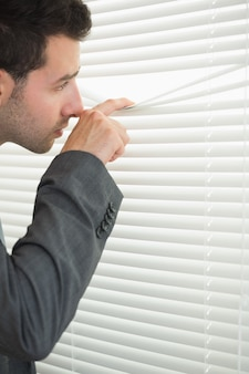 Handsome serious businessman spying through roller blind