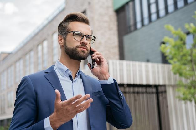 Красивый серьезный бизнесмен разговаривает по мобильному телефону, гуляя по улице