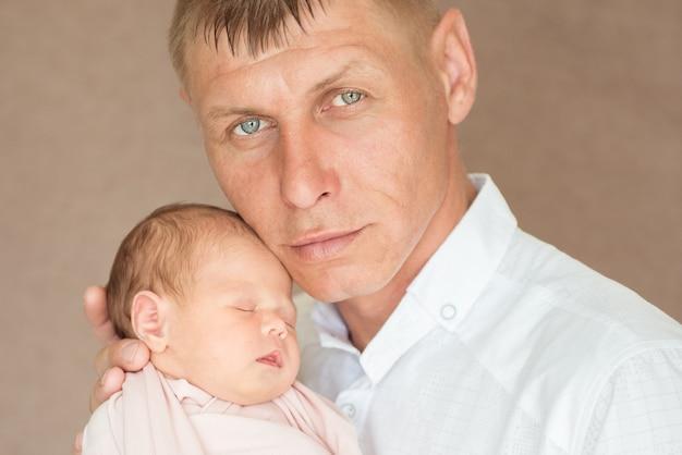 잘 생긴 심각한 아버지는 신생아 딸을 포용합니다. 아버지의 개념
