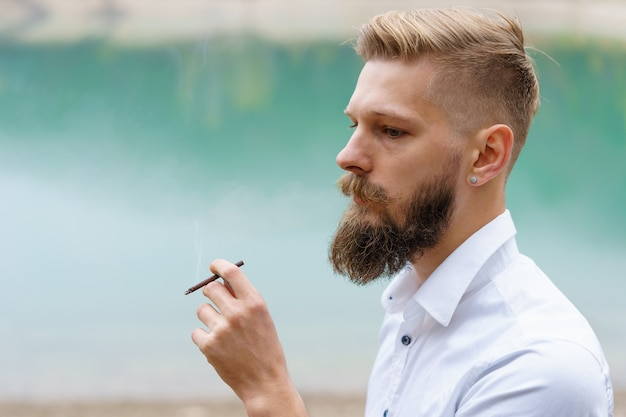 Handsome serious guy young thoughtful man smokes heating tobacco products system outdoors on the bac...