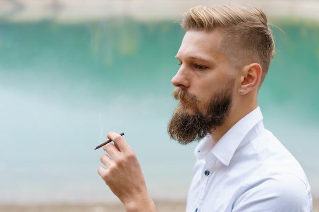 잘생긴 진지한 남자 사려깊은 젊은이는 야외에서 담배 제품 시스템을 가열하는 담배를 피우고 있습니다.