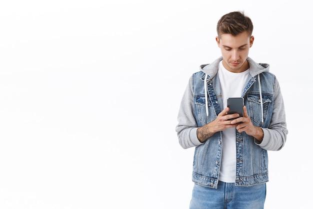 휴대 전화를 사용하는 잘생긴 진지한 금발 남자, 스마트폰 디스플레이 집중, 응용 프로그램 사용, 저녁 데이트를 찾기 위해 앱 업로드, 친구에게 문자 보내기, 온라인 연락 유지