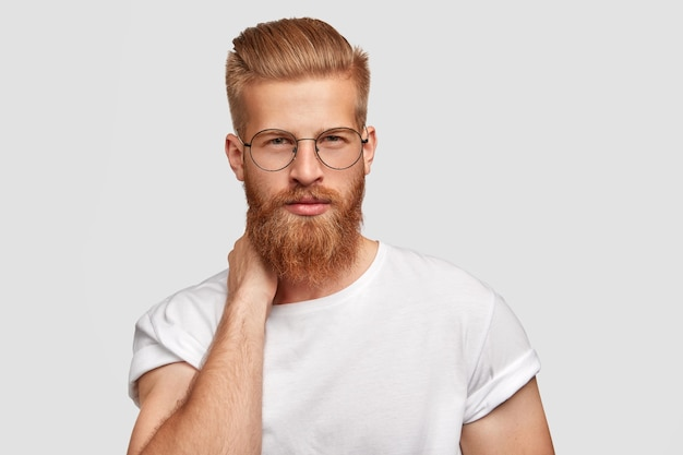 Handsome serious man boss has trendy haircut and ginger beard, keeps hands behind neck, looks confidently