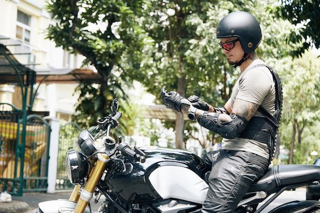 Красивый серьезный мужчина сидит на мотоцикле и надевает кожаные перчатки и шлем для защиты