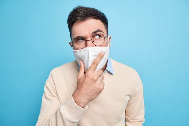 Handsome serious man wears protective mask against coronavirus looks seriously aside points with index finger thinks about vaccination dressed in casual jumper