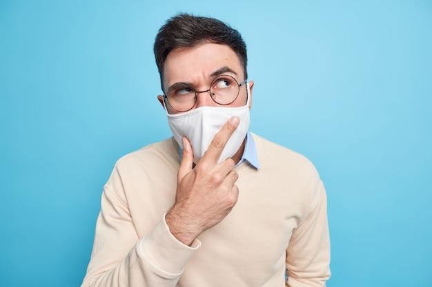 Красивый серьезный мужчина в защитной маске от коронавируса серьезно смотрит в сторону указывает указательным пальцем, думает о вакцинации, одет в повседневный джемпер