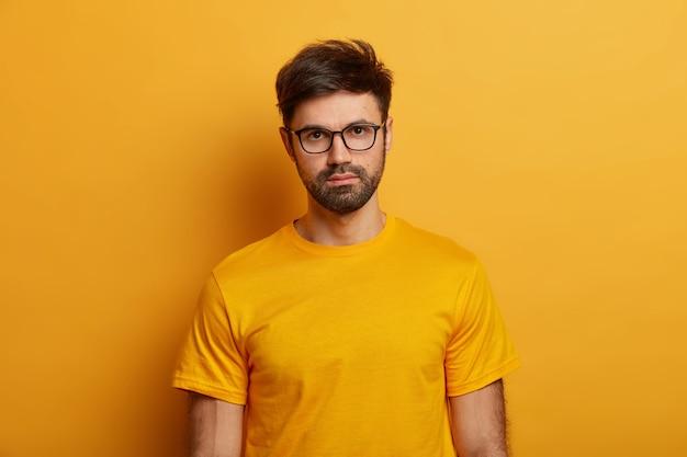 Красивый серьезный мужчина с бородой в очках и футболке