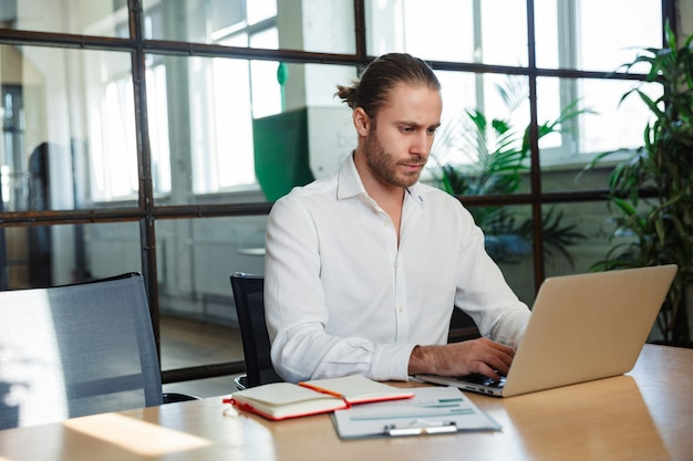 現代のオフィスのテーブルに座っている間ラップトップで作業している無精ひげを持つハンサムな真面目な男