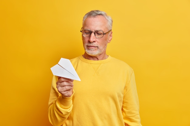 Handsome serious wise grey haired mature man holds handmade paper aircraft going to implement idea dressed in casual jumper and spectacles isolated over yellow wall