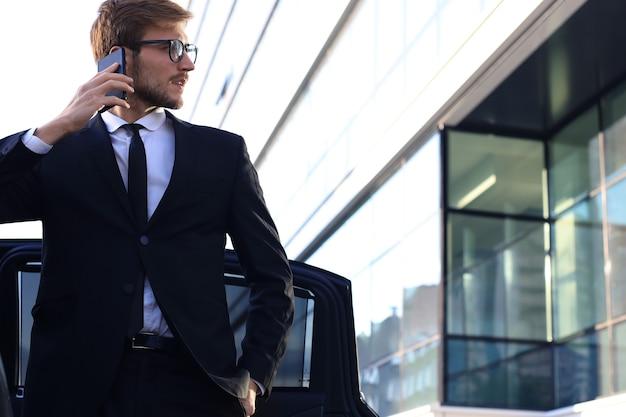 그의 편안한 새 차 근처에 서서 사무실에 가는 잘생긴 진지한 젊은 사업가.