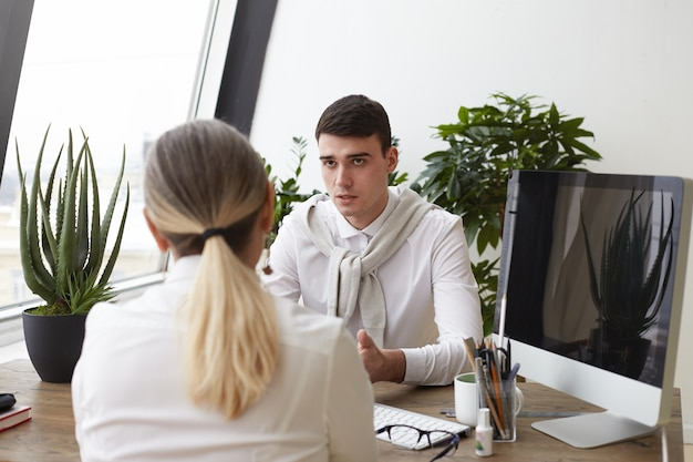 Handsome serious young man hr specialist interviewing unrecognizable female with ponytail during job interview, asking questions about her experience and skills. employment and human resources