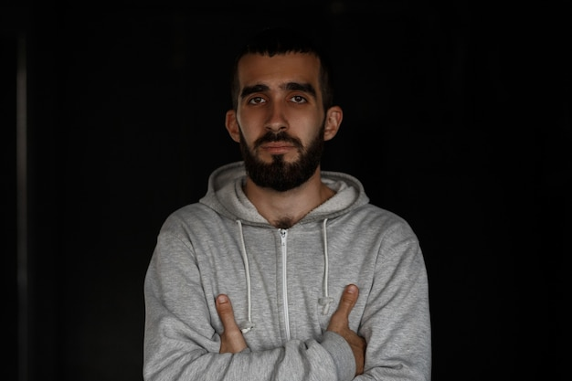 Handsome serious young man with a beard in a gray sweatshirt stands near a black wall