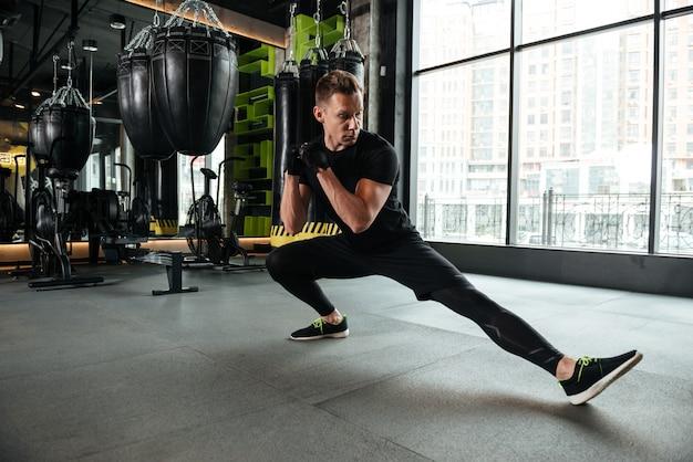 ハンサムな深刻な若いスポーツマンはストレッチ体操を行う