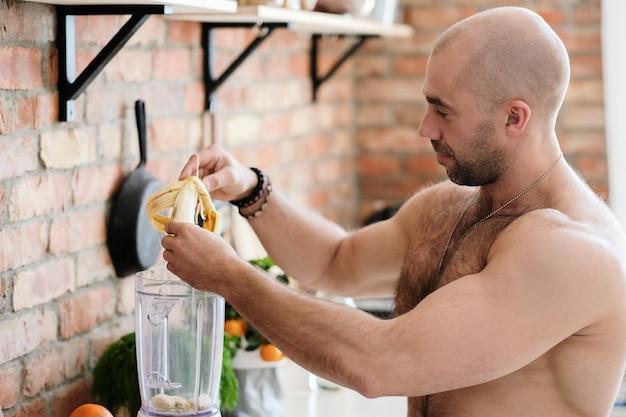 キッチンでハンサムな上半身裸の男