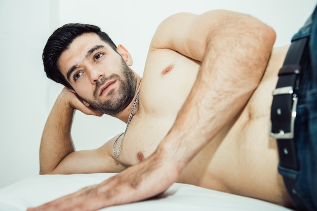 Handsome shirtless man laying on bed and have positive thinking with looking away. seductive attitude and nice attitude sexy concept