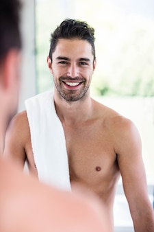 Handsome shirtless man looking in the mirror in the bathroom