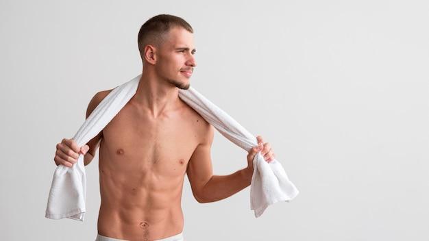 Uomo senza camicia bello che posa con l'asciugamano