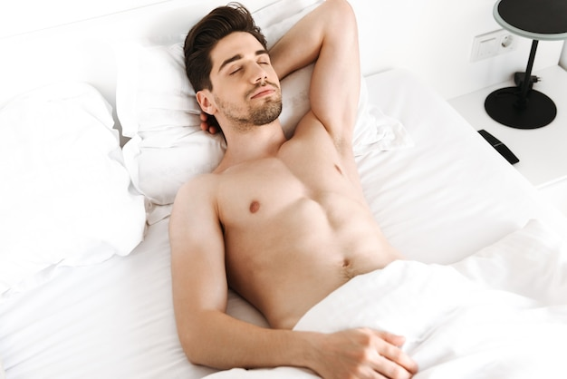 ベッドで寝ているハンサムな上半身裸の男