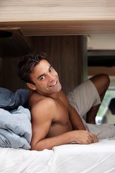 彼のバンで旅行しているハンサムな上半身裸の男