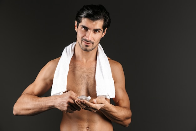 Handsome shirtless man with towel on his shoulders standing isolated, applying aftershave