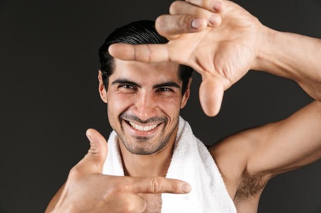 Красивый мужчина без рубашки с полотенцем на плечах стоит изолированно, делая каркас руками