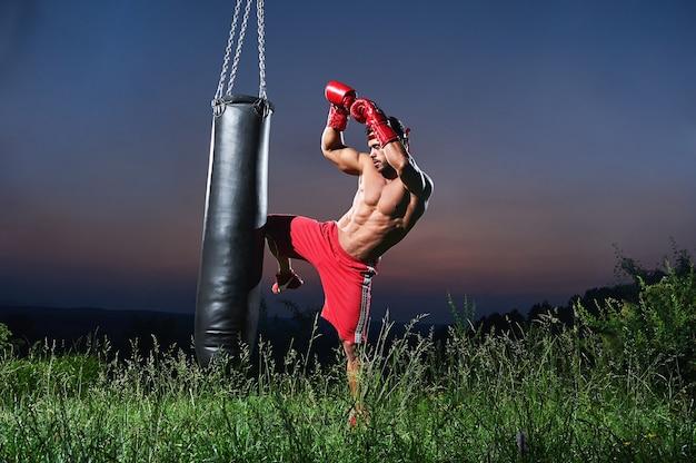 잘생긴 벗은 근육질의 젊은 킥복서는 야외에서 펀칭백으로 운동을 하고 있습니다. 배경에는 아름다운 일몰이 있습니다.