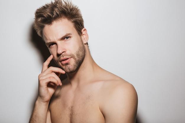 ハンサムな上半身裸の魅惑的な若い男が白い壁に孤立してポーズをとって、正面を見て