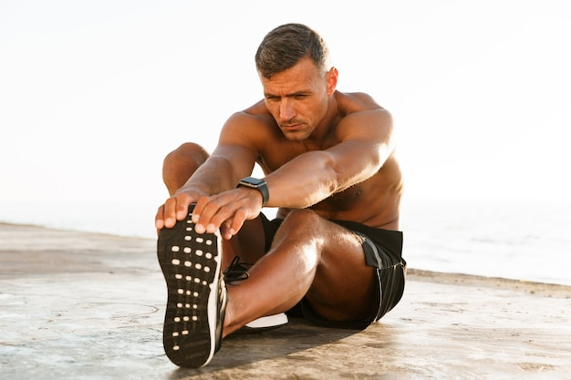 Handsome shirtless sportsman doing stretching