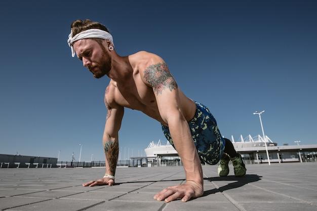 明るい晴れた日に屋外のトレーニンググラウンドで腕立て伏せ運動をしている目をそらしているハンサムな上半身裸のスポーツマン。スポーツライフスタイル。