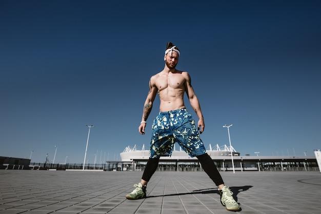 明るい晴れた日に屋外のトレーニンググラウンドでストレッチ運動をしている目をそらしているハンサムな上半身裸のスポーツマン。スポーツライフスタイル。
