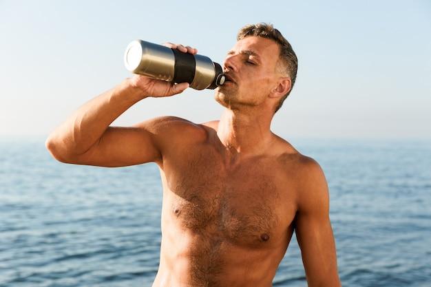 イヤホンでハンサムな上半身裸のスポーツマン