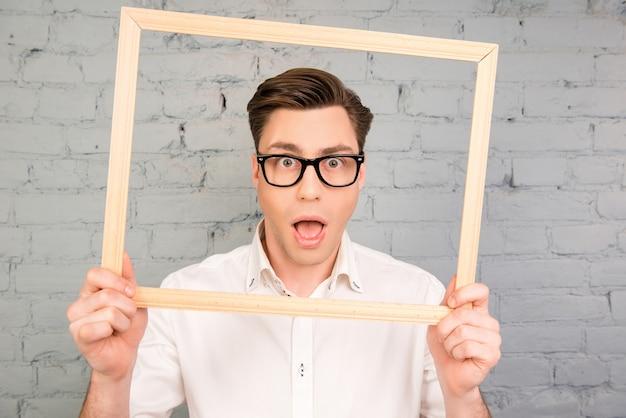 フレームを保持している口を開けてメガネでハンサムなショックを受けた男