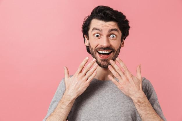 Красивый шокированный молодой бородатый брюнет в свитере стоит над розовым, празднуя