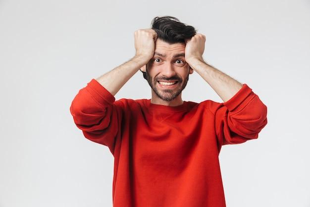 Красивый шокирован молодой бородатый брюнетка мужчина в свитере стоит над белой, празднуя