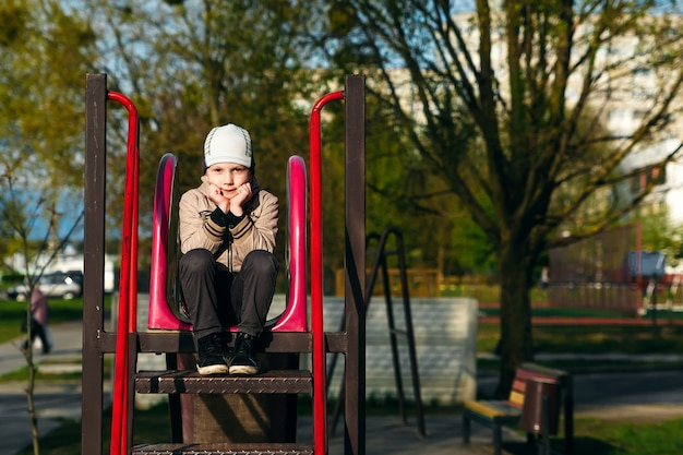 A handsome six year boy is bored sitting on the playground.