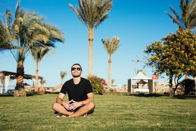 녹색 잔디에 앉아 선글라스에 잘 생긴 슬림 수염 남자는 여름 휴가를 즐길 수 있습니다.