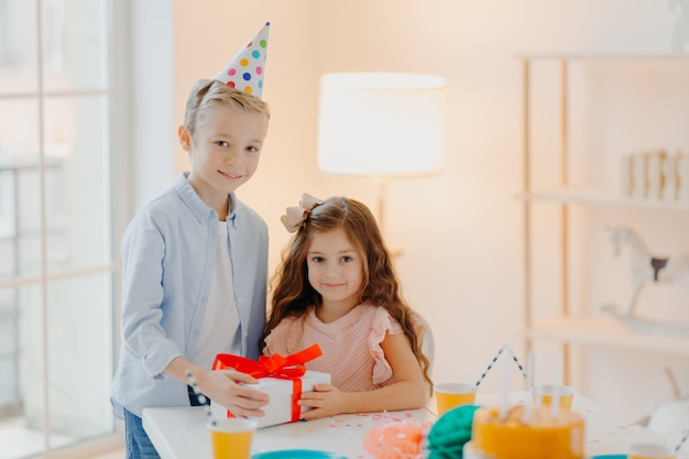 Handsome small boy gives present box to girl, celebrate birthday together