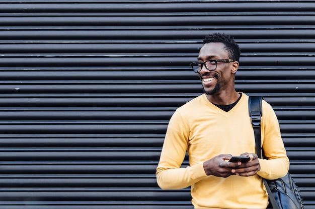 Мобильный телефон красивого умного африканского человека печатая на улице. концепция связи