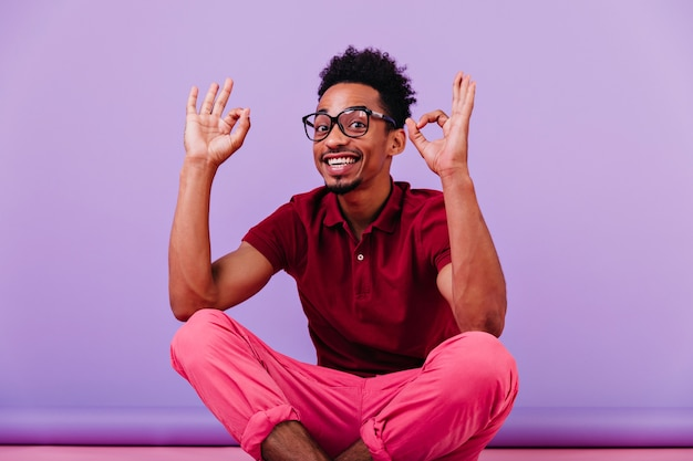 Handsome smart guy making funny faces. laughing black man in good mood posing in glasses.