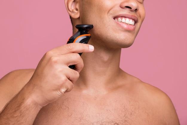 Uomo bello di smiley utilizzando un rasoio elettrico