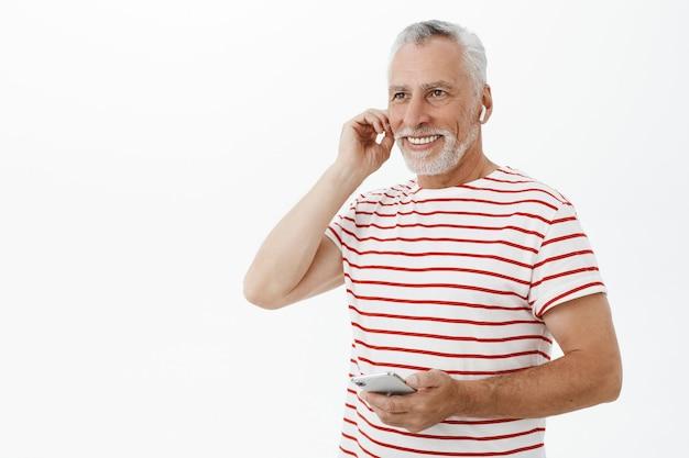 Красивый улыбающийся взрослый бородатый мужчина с помощью беспроводных наушников и смартфона